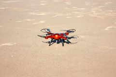 Orange drone standing on the sand. Sunny day. Royalty Free Stock Photo