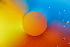 Orange drop on colourful background. Royalty Free Stock Photo