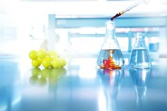 Orange drop solution into water in glass flask with chemical yel. Orange drop solution into blue water in glass flask with chemical yellow structure in science Stock Photo