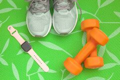 Free Orange Dumbbells, Women`s Sneakers And A Fitness Watch To Control Your Health On A Green Background Royalty Free Stock Images - 181223869