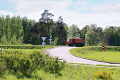 Orange Dump Truck moves on road on hill in green grass Stock Photo