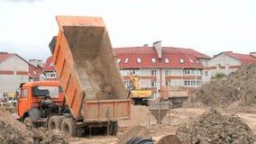Orange dump trucks working on a construction site stock video