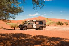 Safari jeep between orange dunes in Namibia. Landscape in Namib Desert, Namibia. Orange dunes in the Sossusvlei, Namibia, West Africa, with camel thorn tree and Royalty Free Stock Images