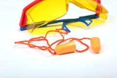 Orange earplug and safety glasses for work. Earplug to reduce noise on a white background . Orange earplug and safety glasses for work. Earplug to reduce noise stock photos