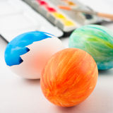 Orange easter egg. Two complete and one half painted easter egg with watercolor palette an brush in background royalty free stock photography