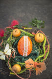 Orange easter egg in bird's nest with decoration on wooden table Royalty Free Stock Photo