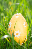 Orange easter egg nestled in the grass Stock Images