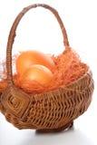 Orange easter eggs in basket Royalty Free Stock Photo