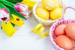 Two baskets of colorful Easter eggs and a bouquet of tulips. White wooden background. Easter holiday concept royalty free stock photo