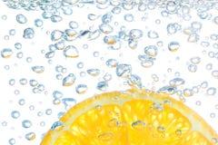 Orange in einer Flüssigkeit mit Luftblasen. Lizenzfreies Stockbild