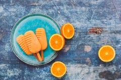 Orange Eiscremeeis am stiel und frische Orangen Stockfotografie