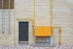 Orange electric box outside modern building. Close up bright orange electrical board and grey door stock photos