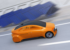 Orange electric car driving on the highway.  Solar panel station on the roadside Royalty Free Stock Photography