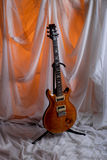 Orange electric guitar in studio setting. Electric six string guitar on stand in studio setting stock images