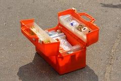 Orange emergency medical pack open in the asphalt road Stock Photos