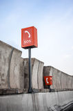 SOS sign and phone box on highway. Orange emergency SOS phone sign and phone box on highway Royalty Free Stock Photo