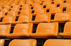 Orange Empty plastic seats at stadium Royalty Free Stock Images