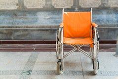 Orange empty wheelchair Stock Photo