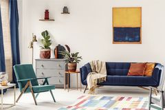 Orange end table with fresh plant standing next to navy couch wi. Th blanket and pillows in white living room interior with painting, green armchair, vases on royalty free stock images