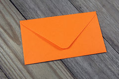 Orange envelope on wooden background. Closeup of orange envelope on wooden background royalty free stock image