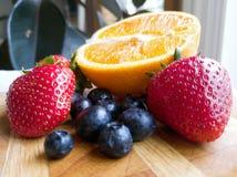Orange Erdbeerblaubeerfrüchte auf hölzernem Schneidebrett Lizenzfreie Stockbilder