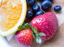 Orange Erdbeerblaubeerfrüchte auf hölzernem Schneidebrett Lizenzfreie Stockfotos