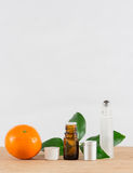 Orange Essential Oil Bottle With White Cap, Citrus Leaves and Roller Bottle Royalty Free Stock Photo