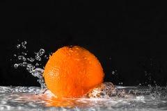 Orange et eau d'éclaboussure au-dessus de fond noir Photo stock