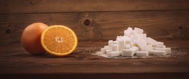 Orange et groupe frais de cubes en sucre avec du sucre granulé Photos libres de droits