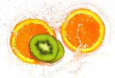 Orange et kiwi dans le blanc de l'eau Images stock