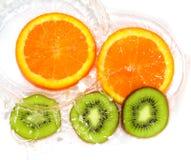 Orange et kiwi dans le blanc de l'eau Image stock