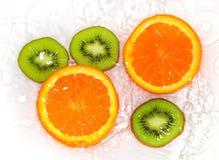 Orange et kiwi dans le blanc de l'eau Photographie stock libre de droits