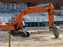 Orange excavator. An orange excavator in front of bleachers on a new football field Stock Photography