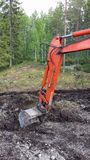 Orange excavator arm digging in mud. With forest background royalty free stock images