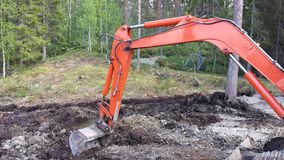 Orange excavator arm digging in mud. With forest background stock images