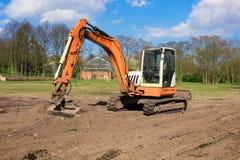Orange excavator on a construction site Royalty Free Stock Photos
