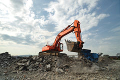 Orange excavator excavating on site Stock Images