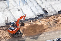 Orange excavator on foundation works. Orange excavator on foundation work Royalty Free Stock Photo
