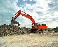 Orange excavator isolated Stock Images