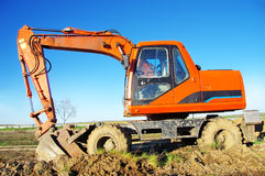 Orange excavator on a platform Royalty Free Stock Photo