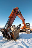 Orange excavator in snow Royalty Free Stock Images