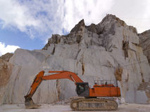 Orange Excavator in a white marble quarry in Carrara Royalty Free Stock Images