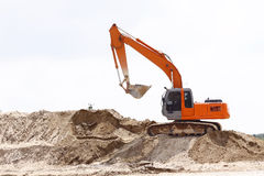 Excavator on sand pile Stock Photos