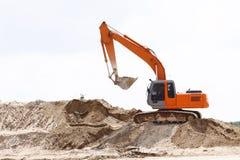 Excavator on sand pile Stock Photos