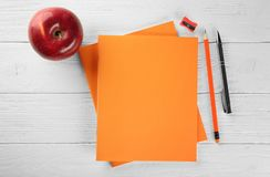 Orange exercise books and fresh red apple Stock Photo