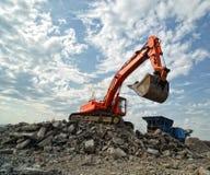 Orange Exkavator auf Baustelle Lizenzfreies Stockfoto