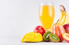 Orange exotic juice of different fruits - mango, kiwi, banana, pear, peach - with ingredients on white wooden background, closeup. Orange exotic juice of stock photo