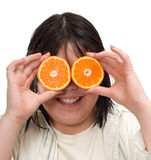 Orange Eyes. Closeup view of a young girl holding orange slices up for eyes, isolated against a white background Stock Photo