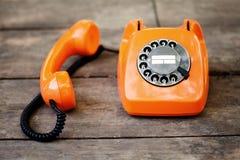 Orange färg för upptagen retro telefon, handset mottagare på trätexturerad bakgrund Fältfotografi för grunt djup royaltyfria bilder