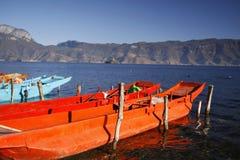 Orange färg för Wood fiskebåtfisher som svävar på Lugu för blått vatten som den sceniska fläcken för sjö omges av snöberget och h Arkivbild